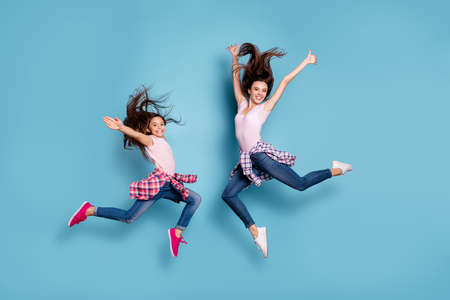 Photo pour Full length body size view portrait of two nice attractive cheerful careless carefree sportive straight-haired girls having fun hipster look isolated on bright vivid shine blue turquoise background - image libre de droit
