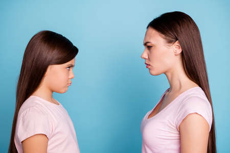 Foto de Close-up profile side view portrait of two nice attractive offended irritated straight-haired girls looking frowning at each other isolated over bright vivid shine green blue turquoise background - Imagen libre de derechos