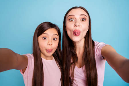 Foto de Self-portrait of two nice cute charming attractive crazy girlish cheerful comic childish straight-haired girls having fun time good mood isolated on bright vivid shine green blue turquoise background - Imagen libre de derechos