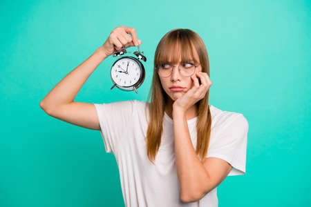 Foto de Close up photo amazing beautiful she her lady hold raise arm hand metal alarm clock missed work bad mood afraid to be fired wear specs casual white t-shirt clothes isolated teal green background - Imagen libre de derechos