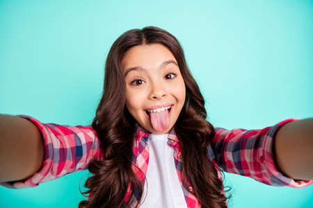 Foto de Self-portrait of her she nice attractive crazy naughty cheerful wavy-haired pre-teen girl wearing checked shirt grimacing isolated over bright vivid shine green blue turquoise background - Imagen libre de derechos