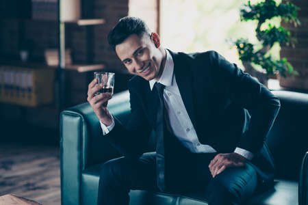 Photo pour Close up photo handsome he him his perfect white teeth hands arms whisky beverage enjoy pause break toasting wear formal-wear dress code shirt jacket tie suit costume sit chair indoors office place - image libre de droit