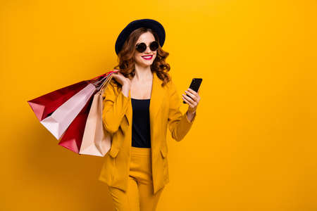 Foto de Close up photo beautiful she her lady hands arms telephone many packs buyer vacation traveler sale discount search gps next boutique wear specs formal-wear suit isolated yellow bright background - Imagen libre de derechos