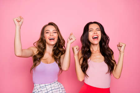 Foto de Portrait of charming nice pretty youth delighted positive cheerful content candid rejoice scream shout yeah raise hands fists reaction wear modern youngster clothing isolated pink background - Imagen libre de derechos