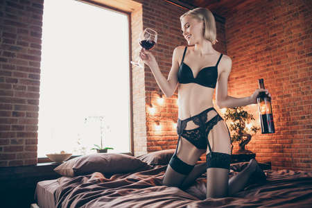 Photo pour Close up photo overjoyed beautiful tender gorgeous amazing she her lady little drunk arms hands raise bottle alcohol beverage wineglass dancer herself self sheets excited bikini boudoir room indoors - image libre de droit