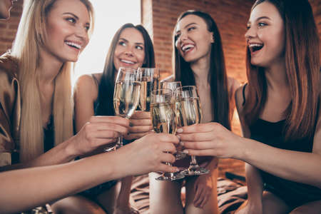 Photo for Cropped close up photo five amazing beautiful she her ladies hands arms glasses festive golden beverage short nightie sit sheets clink listen tell talk toasts sleep costumes girls night room indoors - Royalty Free Image