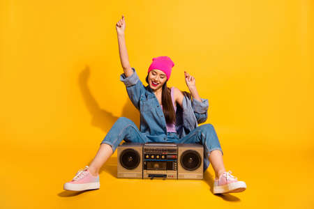 Photo for Full length body size photo beautiful she her lady enjoy weekend vacation vintage audio recorder sit floor motion wear casual jeans denim jacket shoes pink hat isolated yellow vivid bright background - Royalty Free Image