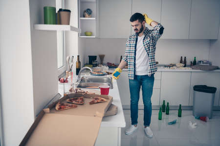 Photo pour Portrait of nice attractive minded pensive unsure bearded guy wearing checked shirt mess chaos around maid order service in modern light white interior style kitchen indoors - image libre de droit