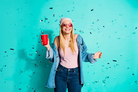 Foto de Portrait of nice charming cute lovely trendy cheery girl wearing sun eyeglasses eyewear holding in hand red cup enjoy rest relax isolated on bright vivid shine blue green turquoise background - Imagen libre de derechos