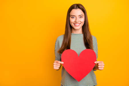 Photo for Photo of nice beautiful charming enchanting girl holding red heart of love in order to celebrate her boyfriend while isolated with yellow background - Royalty Free Image