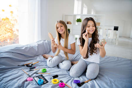 Photo pour Portrait of attractive children people hold hand apply cosmetics feel leisure content dreamy sit white bed room indoors - image libre de droit