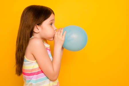 Photo pour Profile side photo of charming kid inflating baloon isolated over yellow background - image libre de droit