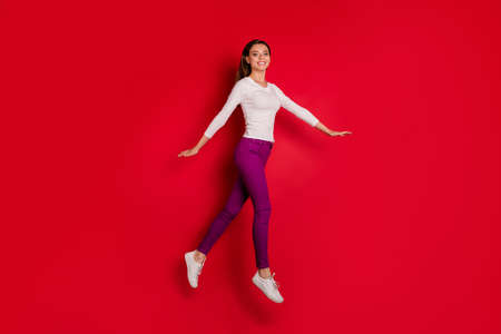 Foto de Full length body size photo of sporty girl running even without sportswear while isolated with red background - Imagen libre de derechos