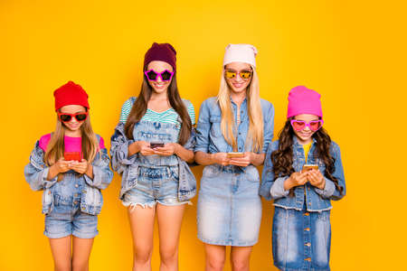 Photo pour Close-up photo of group of four people influencers using posting following subscribing new sites searching news reading news-feed wearing hat cap sunglass isolated bright background - image libre de droit
