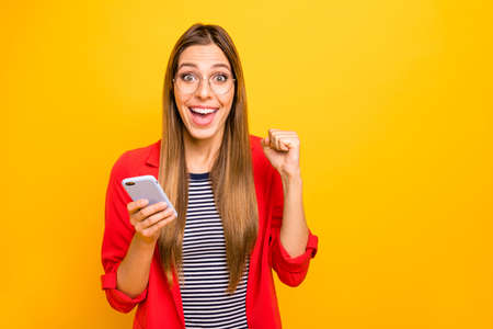 Foto de Portrait of impressed lady with eyeglasses eyewear holding device raising fists screaming yeah wow omg isolated over yellow background - Imagen libre de derechos