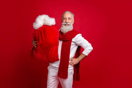 Photo for Stylish aged man improvisation modern santa with large bag wear sweater white pants isolated red background - Royalty Free Image