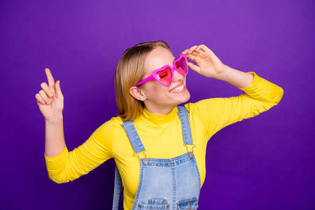 Photo for Portrait of cheerful youth touching her specks closing eyes wearing yellow turtleneck denim jeans overalls isolated over purpl violet background - Royalty Free Image