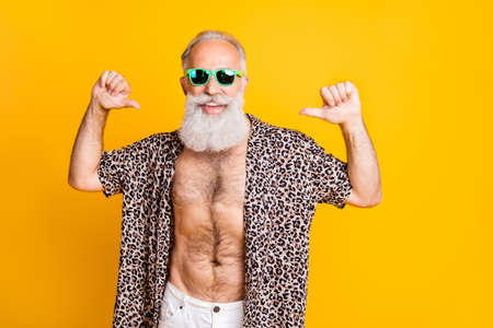 Foto de Photo of old man thumbing at himself being proud and advertising himself while isolated with yellow background - Imagen libre de derechos