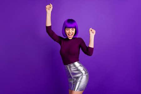 Foto de Portrait of cheerful lady raising her fists screaming yeah wearing turtleneck isolated over purple violet background - Imagen libre de derechos