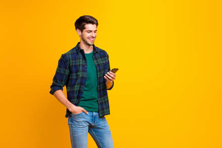 Photo pour Photo of blogger guy holding telephone in hands checking subscribers wear casual checkered shirt and jeans isolated yellow color background - image libre de droit