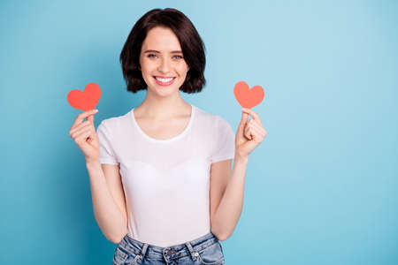 Photo pour Portrait of her she nice attractive lovely sweet winsome cheerful cheery girl holding in hands two heart symbol cards isolated on bright vivid shine vibrant blue turquoise color background - image libre de droit