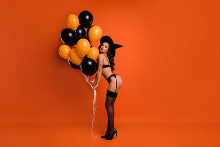 Foto de Full size photo of beautiful nude lady hold air balloons make private party showing husband ideal figure wear black bikini tights witch cap isolated orange background - Imagen libre de derechos