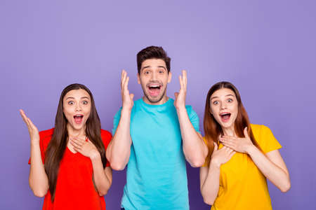 Foto de Portrait of nice-looking attractive lovely charming cheerful cheery guys wearing colorful t-shirts showing astonishment expression isolated over violet lilac background - Imagen libre de derechos