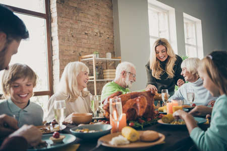 Foto de Photo of big full family reunion gathering sit feast dishes dinner table young wife giving old parents fresh bakery multi-generation in evening living room indoors - Imagen libre de derechos
