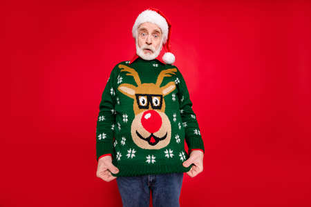 Photo pour Photo of santa granddad showing ugly deer ornament pullover dressed on himself not understand idea of costume theme x-mas parties isolated red background - image libre de droit