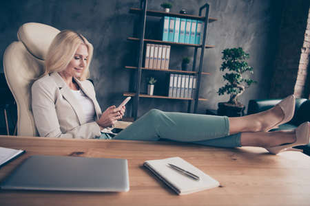 Foto de Portrait of charming middle aged blonde hair woman use cellphone have chat with her workforce career partners type messages sit in chair put her high-heels on wooden table - Imagen libre de derechos