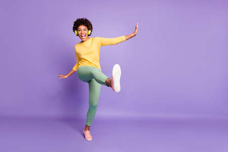 Foto de Full length body size photo of wavy cheerful excited ecstatic overjoyed shouting girlfriend dancing listening to music pretending to be kicking with leg near empty space isolated over violet color pastel background - Imagen libre de derechos