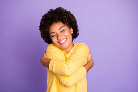 Foto de Photo of charming sweet pretty girlish feminine youngster hugging herself smiling toothily enjoying her newly bought yellow sweater of coziness isolated over pastel purple color background - Imagen libre de derechos