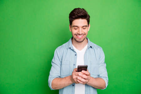 Photo pour Photo of cheerful positive modern guy browsing through his telephone looking for information isolated over green vivid color background - image libre de droit