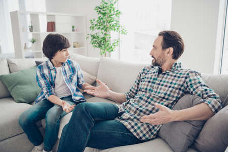 Photo pour Portrait of two nice attractive friendly guys dad and pre-teen son sitting on couch discussing psychology generation problems in light white modern style interior living-room - image libre de droit
