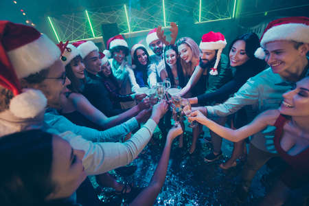 Photo for Photo of party crowd best friends holding sparkling wine glasses counting last seconds to newyear festive mood wear dresses shirts pants santa hat in night club - Royalty Free Image
