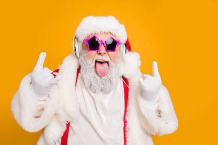 Photo for Close up photo of crazy funny hipster santa claus show horns sign tongue-out want rock-and-roll concert instead x-mas tradition celebration wear hat trendy suspenders isolated yellow color background - Royalty Free Image