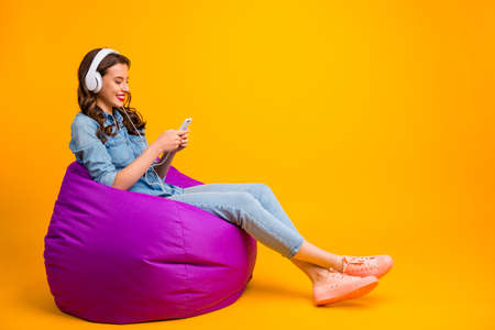 Photo pour Profile side view of her she nice attractive lovely cheerful cheery wavy-haired girl sitting on bag chair listening modern music isolated on bright vivid shine vibrant yellow color background - image libre de droit