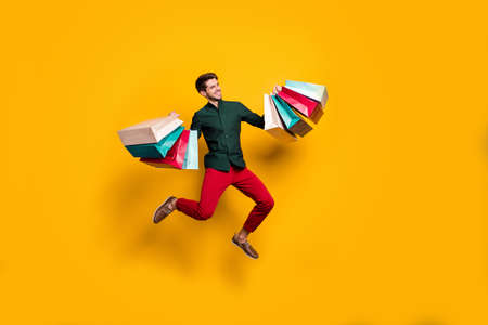 Foto de Full length body size photo of cheerful positive handsome jumping man holding numerous packages returning from shopping mall isolated vivid color background - Imagen libre de derechos