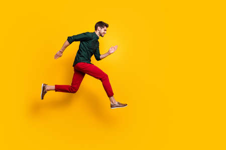 Foto de Full body profile side photo of positive cheerful funky guy hear about wonderful black friday sales jump run want be first wear casual style outfit isolated over yellow color background - Imagen libre de derechos