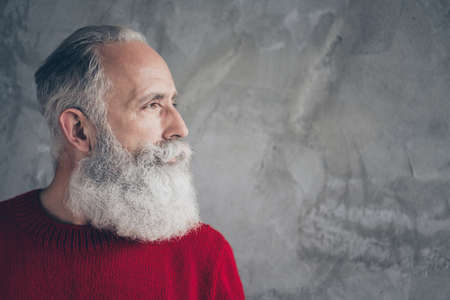 Photo pour Closeup photo of nice aged guy looking side empty space minded wear red knitted pullover jumper cool hipster santa outfit isolated grey color concrete wall background - image libre de droit