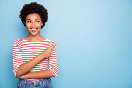 Photo for Photo of cheerful positive sweet pretty girlfriend standing confidently pointing into empty space smiling toothily in jeans denim isolated pastel blue color background - Royalty Free Image