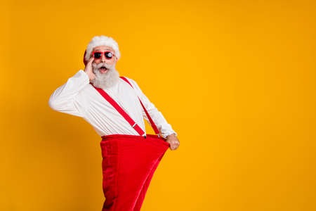 Foto de Profile side photo of crazy funky white beard hair santa claus in hat hold big size pants lose weight x-mas celebrate noel diet effect scream isolated yellow color background - Imagen libre de derechos