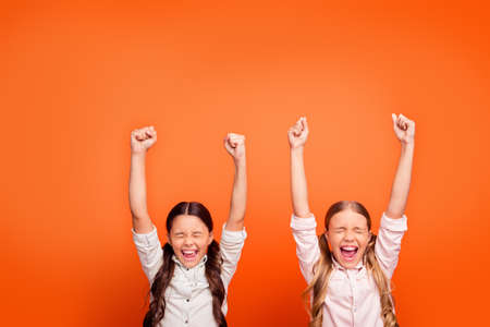 Foto de Yeah unbelievable victory. Portrait of lucky delighted crazy two kids girls win contest feel euphoria scream raise fists wear modern clothing isolated orange color background - Imagen libre de derechos