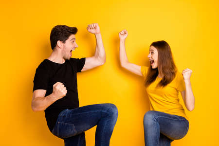 Photo pour Photo of crazy rejoicing boyfriend and girlfriend overjoyed about sales and discounts where they bought jeans denim black t-shirt isolated over vivid yellow color background - image libre de droit