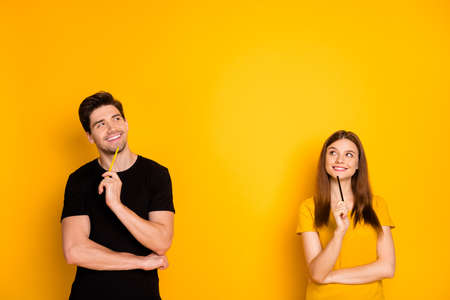 Photo for Photo of cheerful positive cute nice charming pretty couple holding pens wearing black t-shirt smiling toothily looking into empty space a fit of thoughts isolated over bright shiny color background - Royalty Free Image