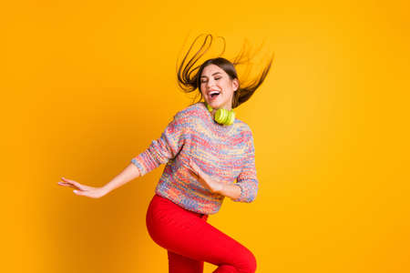 Photo for Portrait of positive cheerful funky girl listen music on head phones enjoy start dance dancing floor wear pullover red pants trousers isolated over shine color background - Royalty Free Image