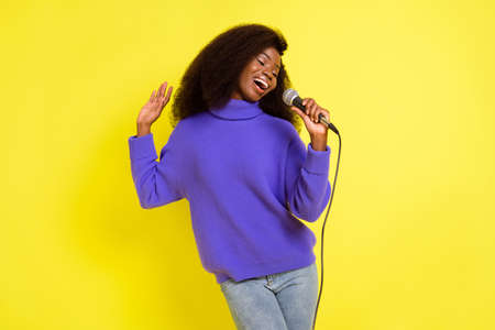 Photo of pretty dark skin lady hand hold mic singing have good mood isolated on yellow color background