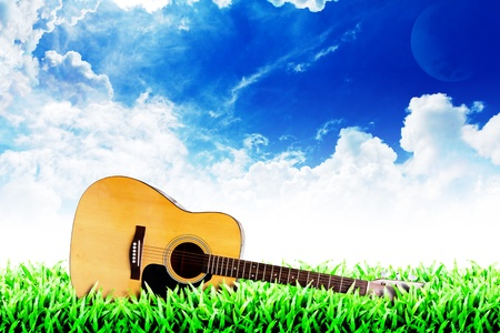Photo pour Grass field and cloudy sky background : guitar on the grass  - image libre de droit