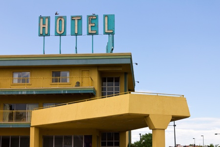 An old dirty hotel sign with birds perched on top stands above a colorful motel on the side of the highway.