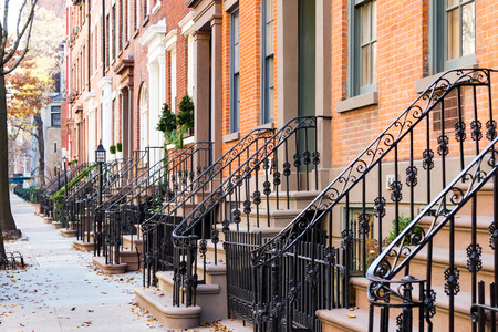Photo for Row of old historic brownstone buildings along an empty sidewalk block in the Greenwich Village neighborhood of Manhattan, New York City NYC - Royalty Free Image